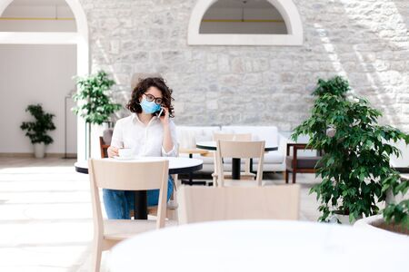 Social distancing during quarantine. Young woman wearing protective mask in empty cafe indoors. Girl talking on mobile phone. Lifestyle moment. Restaurant with safety space between seats in new normal 免版税图像