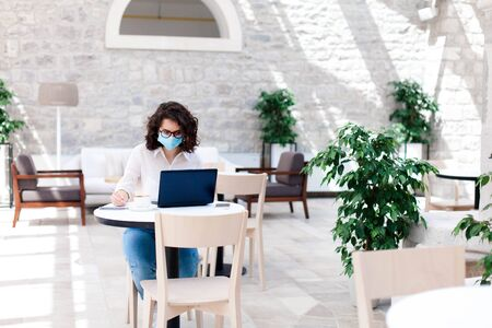 Young woman working safety in cafe indoors. Social distancing during quarantine. Freelancer wearing protective mask, using laptop. Comfortable office, coworking modern workplace with limited seating.