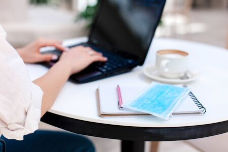 Young woman working at cafe table indoors. Social distancing in office during quarantine. Close up of freelancer hands, protective mask, coffee, laptop and notepad. Coworking modern workplace. 免版税图像