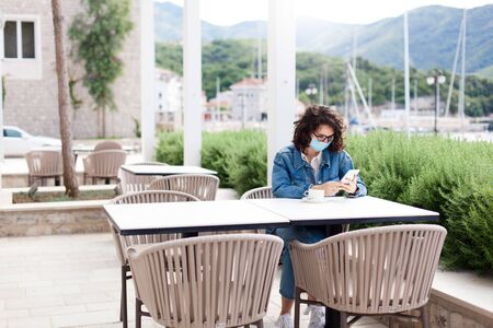 Social distancing during quarantine. Young woman wearing protective mask in empty cafe outdoors. Girl using mobile phone. Lifestyle moment in new normal. Restaurant terrace with safety limited seating 免版税图像