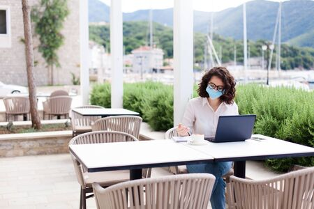 Young woman working safety in empty cafe outdoors. Social distancing during quarantine. Freelancer wearing protective mask, using laptop. Lifestyle moment. Restaurant patio with safety limited seating 免版税图像