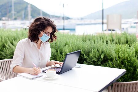 Young woman working safety in empty cafe outdoors. Social distancing during quarantine. Freelancer wearing protective mask, using laptop. Lifestyle moment. Restaurant terrace by sea 免版税图像