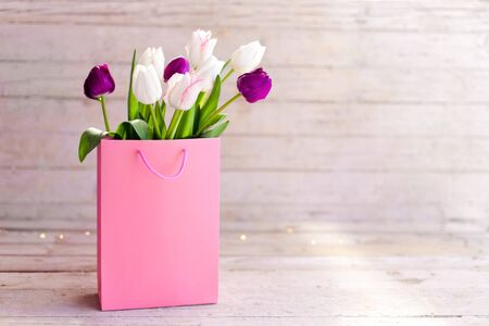 Spring flowers. Blooming tulips in pink shopping bag at wooden background. White, lilac and purple bouquet. Still life in morning sun light. Presents for holidays. Copy space. 免版税图像