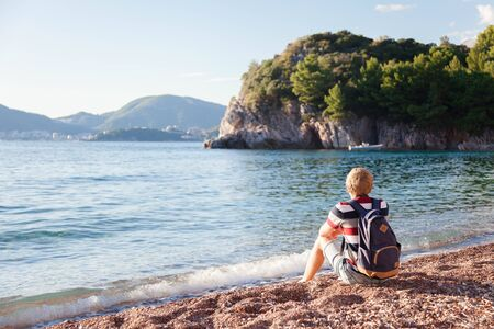 Traveler with backpack sitting at sea beach. Tourist enjoying traveling, summer vacation, adventure, relaxation. Man has rest. Copy space. Rear view. 免版税图像