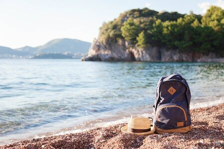 Travel backpack and straw hat at sea beach. Traveler bag on pebbles. Concept of enjoying traveling, summer vacation, trip, outdoor adventure. Copy space. 免版税图像