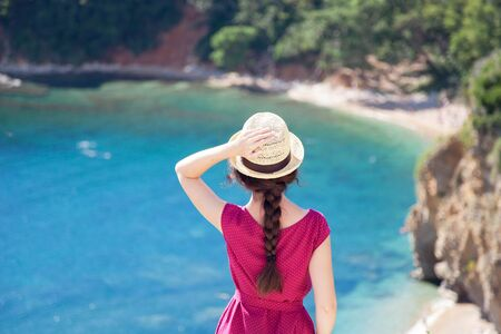 Young graceful woman at sea beach in summer vacation. Rear view of girl traveler in straw hat. Concept of travel, femininity, solo female tourism, holiday, adventure. Lady looking at ocean view. 免版税图像