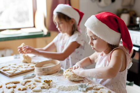 Kids are cooking Christmas gingerbread cookies in cozy home kitchen. Cute children in santa hats play with dough. Little girls make homemade pastries. Lifestyle authentic moment. Children chef concept 免版税图像