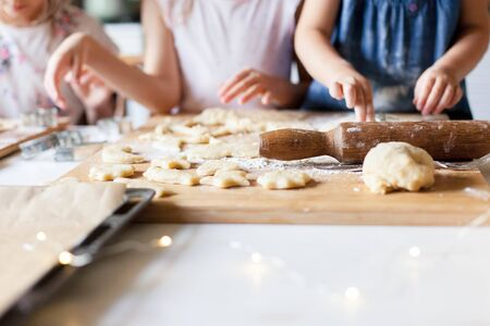 Children hands are cooking Christmas gingerbread cookies in cozy home kitchen. Kids preparation holiday food for family. Little girls bake homemade pastries. Children chef concept.