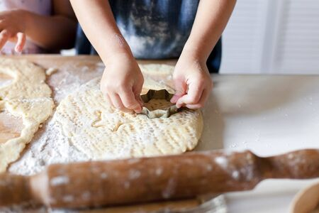 Child hands make Christmas gingerbread cookies in cozy home kitchen. Kids are cooking holiday biscuits for family. Little girls bake homemade pastries. Children chef concept.
