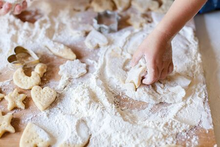 Child hands are cooking Christmas gingerbread cookies in home kitchen. Kid is playing with dough and flour. Little girl bake holiday homemade pastries. Children chef concept.