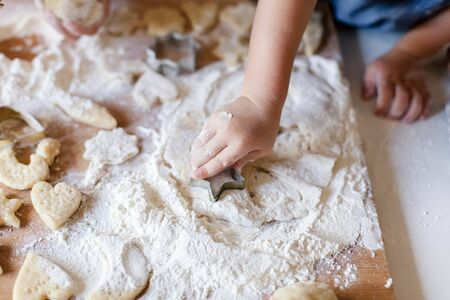 Child hands are cooking Christmas gingerbread cookies in home kitchen. Kid is playing with dough and flour. Little girl preparation holiday homemade pastries. Children chef concept. 免版税图像