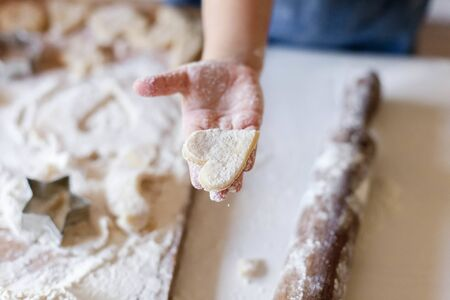 Child holds Christmas gingerbread heart. Kid is cooking homemade cookies in cozy home kitchen. Little girl bakes pastries. Children chef concept.