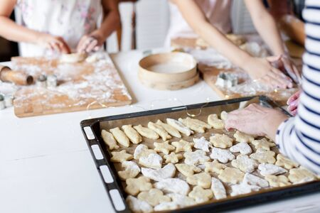 Family is cooking Christmas gingerbread cookies in home kitchen. Baking homemade pastries on oven tray. Children chef concept. Close up of hands.