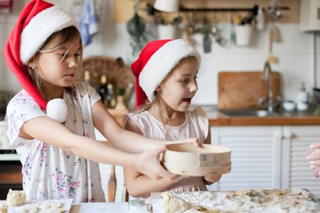 Children are cooking Christmas cookies in cozy home kitchen. Cute kids prepare holiday food for family. Funny little sisters in flour make New Year meal. Children chef concept. Lifestyle candid moment