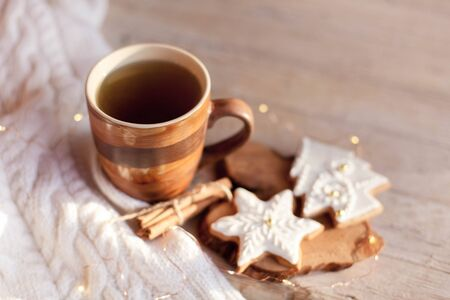 Christmas tea time. Mug of hot steamy beverage, gingerbread cookies at wooden and knitted background. Cozy morning breakfast with homemade sweets and cup. Winter food, drinks, new year lights. 免版税图像