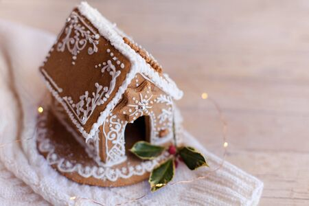 Gingerbread house, Christmas cozy decorations on wooden and knitted background with glares. Handmade sweets is decorated with holly berries and cute white ornaments, new year lights, garland.