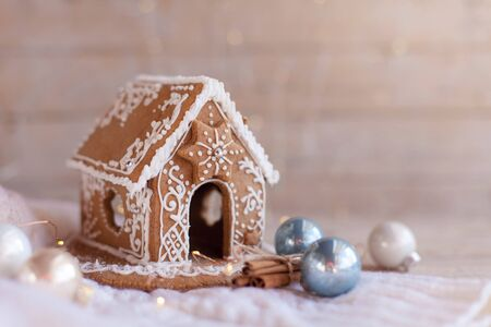 Gingerbread house, Christmas cozy decorations on wooden and knitted background with glares. Handmade sweets is decorated with holly, blue and white ornaments, new year lights, garland.