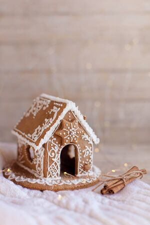 Gingerbread house, Christmas cozy decorations on wooden and knitted background with glares. Cinnamon sticks like firewood. Handmade building is decorated with white ornaments, new year lights.