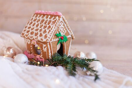 Gingerbread house, Christmas decorations on wooden background with glares. Homemade sweets is decorated with fir branch, new year lights, garland and cute white and pink ornaments. Foto de archivo