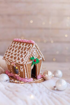 Christmas gingerbread house, decorations on wooden background with glares. Homemade sweets is decorated with holly, new year lights, garland and cute white and pink ornaments. 免版税图像