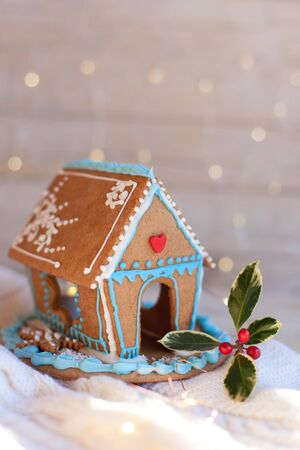 Christmas gingerbread house, decorations on wooden and knitted background with glares. Handmade sweets is decorated with green holly and cute blue, white and red ornaments, new year lights, garland.