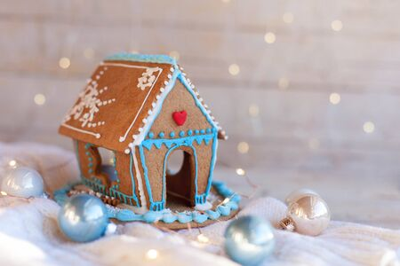 Christmas gingerbread house, decorations on wooden and knitted background with glares. Handmade sweets is decorated with cute blue, white and red ornaments, new year lights, garland. Foto de archivo