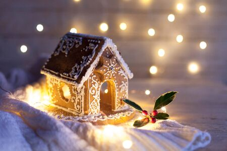 Christmas gingerbread house at night, cozy decorations on wooden and knitted background with glares. Cozy house in warm light with holly berries and cute white ornaments. 免版税图像
