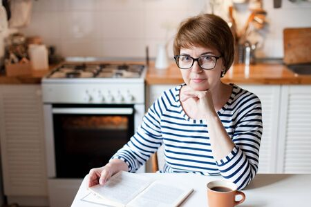 Middle aged woman is reading book and drinking coffee or tea at cozy home kitchen. Senior person has rest from housework and cooking. Happy housewife in spectacles is smiling and using oven indoors. 免版税图像
