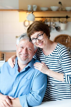 Happy senior couple is hugging and smiling in cozy home kitchen inside. Portrait of middle aged man and woman. Concept of wellbeing, happiness, kindness, male and female health, enjoying retirement.