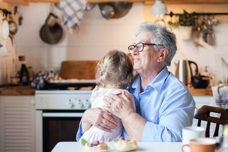 Happy senior woman is hugging child in cozy home kitchen. Grandmother and cute little girl are smiling. Kid is enjoying kindness, warm hands, care, support. Family is cooking together. Banque d'images