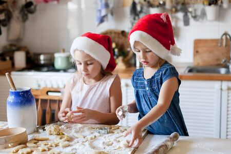 Children are cooking Christmas cookies in cozy home kitchen. Cute kids prepare holiday food for family. Funny little sisters in flour make pastries. Lifestyle candid moment. Children chef concept 免版税图像