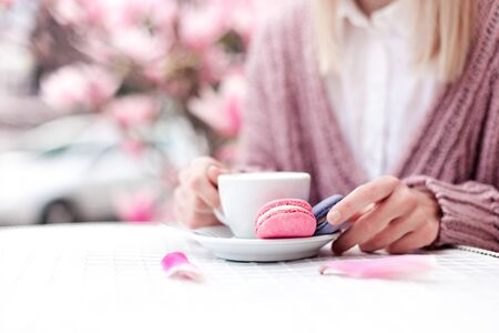 Spring cafe. Young woman drinking coffee with pink macaroons at city streets. Girl enjoying tenderness and morning breakfast outdoor. Blooming magnolia flowers. Close up of female hands. Copy space