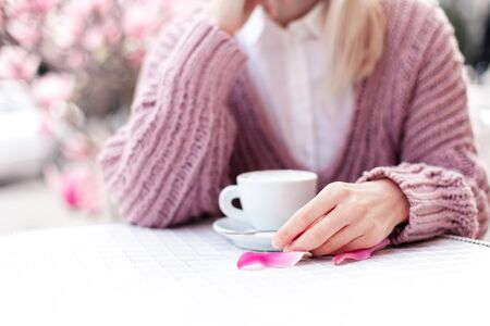Young woman drinking coffee in spring cafe at city streets. Girl enjoying morning breakfast alone. Blooming pink magnolia flowers and petals outdoors. Lifestyle moment. Close up of female hands.