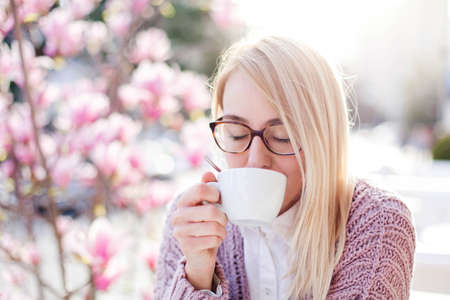 Young woman drinking coffee in spring cafe at city streets. Happy girl enjoying morning breakfast in blooming pink magnolia flowers outdoors. Lifestyle moment. Concept of spring mood, tenderness.