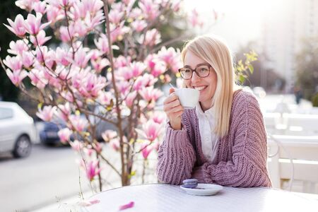 Spring cafe. Young woman drinking coffee at city streets. Attractive happy girl smiling and enjoying sunset outdoors. Blooming bushes of pink magnolia flowers. Lifestyle moment. 免版税图像
