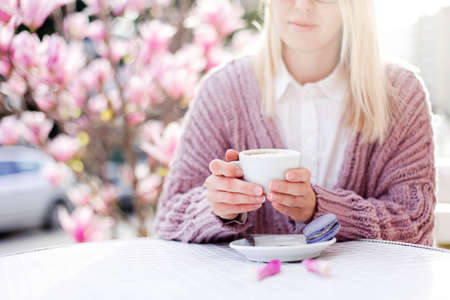 Spring cafe. Young woman drinking coffee with macaroons at city streets. Girl enjoying morning breakfast outdoor. Blooming pink magnolia flowers. Lifestyle moment. Close up of female hands. Copy space 免版税图像