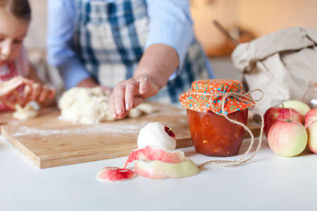 Family is cooking apple pie in cozy home kitchen. Homemade jam, cute orange jar, dough, flour and fall harvest foods are on table. Grandmother and child prepare autumn pastries for Thanksgiving dinner
