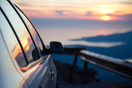 Road trip by car at sunset. Parking on roadside of narrow mountain way. Stop for rest. View of amazing sea coastline. Concept of outdoor adventure, summer vacation. Copy space