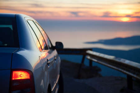 Road trip by car at sunset. Parking on roadside of narrow mountain way. Stop for rest with red headlamp. View of amazing sea coastline. Concept of outdoor adventure, summer vacation. Copy space 免版税图像
