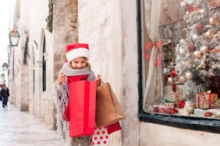 Christmas shopping. Child girl looks into paper bags on market street. Cute kid in red santa hat makes purchase by store showcase decorated with gifts. Cozy fair, New Year and Black Friday