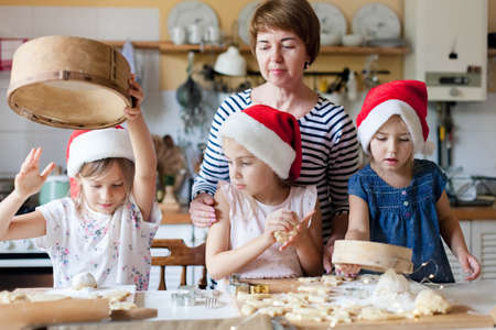 Family is cooking Christmas gingerbread cookies together in cozy home kitchen for dinner. Kids and young grandmother prepare holiday meal. Girls help woman. Lifestyle moment. Children chef concept Foto de archivo