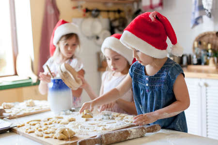 Kids cooking Christmas gingerbread cookies in cozy home kitchen. Funny children chefs in santa hats prepare traditional holiday meal. Cute girls make cake for family. Lifestyle authentic moment.