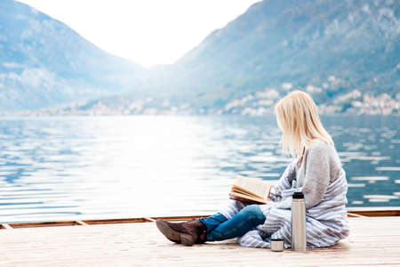 Woman is reading book by winter sea, mountains, beach.