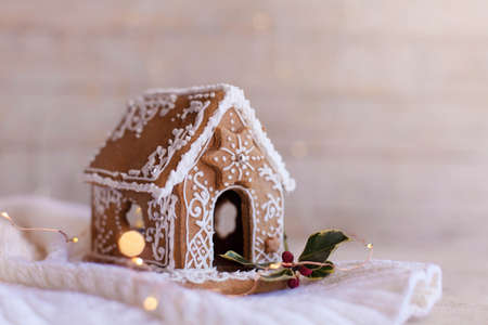 Gingerbread house, Christmas cozy decorations on wooden and knitted background with glares. Handmade cute sweets is decorated with holly berries and white ornaments, new year lights, garland.