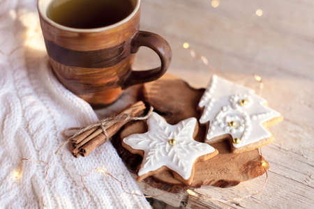 Christmas still life. Gingerbread glazed cookies, cup of tea, cinnamon at wooden background with glares. Cozy tea time with homemade sweets and mug of hot beverage. Winter food, drink, new year lights