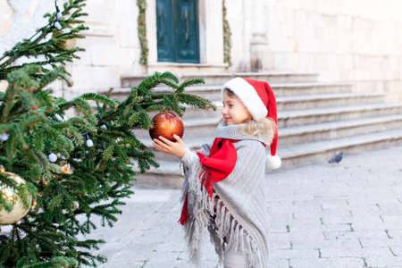 Child is decorating Christmas tree with ornaments outside. Happy kid is enjoying holidays. Little girl in red santa hat at winter market on town street. Cozy fair and New Year in Dubrovnik, Croatia.