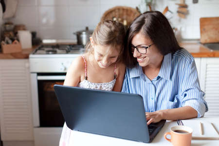 Holiday shopping online. Happy mother and child girl make purchases in the Internet on Black Friday. Cute kid and woman are smiling. Family are enjoying buying gifts with laptop in cozy home kitchen. Stock Photo