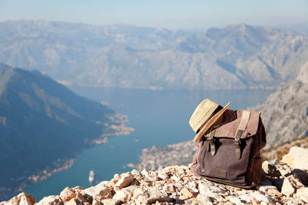 Travel backpack and straw hat in mountains. Traveler bag above amazing view, landscape. Concept of enjoying traveling, vacation, tourism, trip, outdoor adventure. Nature background. Copy space.