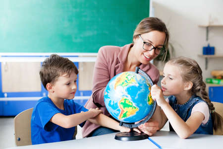 Teacher and kids study the globe at elementary school. Lesson for children in classroom. Kind woman is smiling and teaching her primary students. Back to school concept. Фото со стока