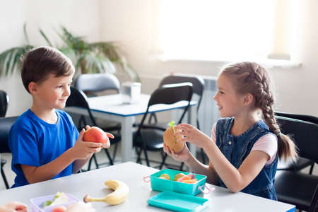 School kids eating healthy food together. Happy children sitting at table with packed lunch boxes. Back to school concept. Boy and girl treat each other fruits.